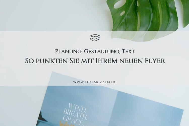 Flyer konzipieren und betexten: Motiv Schreibtisch mit aufgeschlagenem Flyer und Pflanzenblatt
