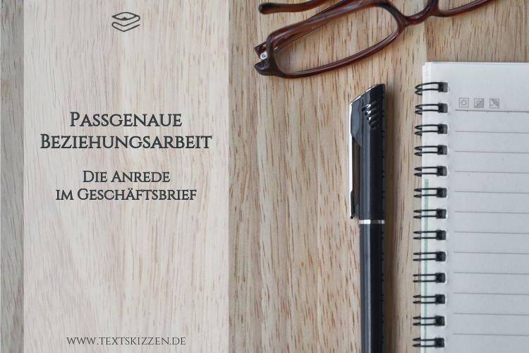 Anrede im Geschäftsbrief: Notizblock, Stift und Brille auf Holztisch