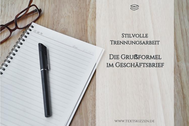 Grußformeln im Geschäftsbrief: Notizblock, Stift und Brille auf Holztisch
