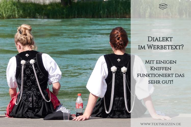 Dialekt in der Werbung: zwei Mädchen im Trachtenkostüm, am Wasser sitzend